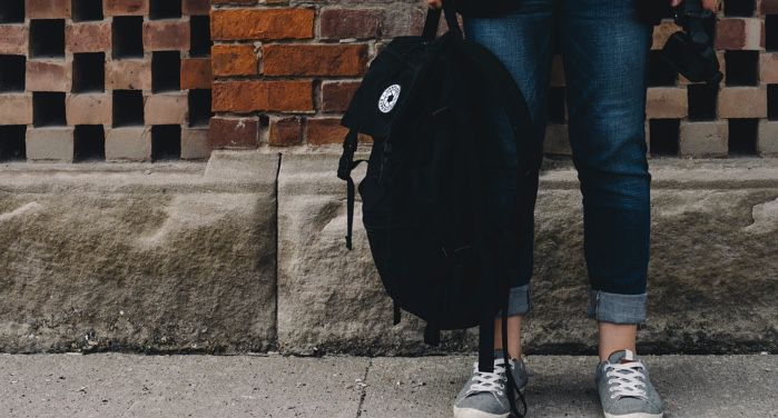 waist down photo of young person holding a black backpack wearing jeans and grey sneakers https://unsplash.com/photos/O0T1SIgHAfM