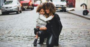 mother kneeling beside toddler daughter in the middle of the street, both smiling at the camera
