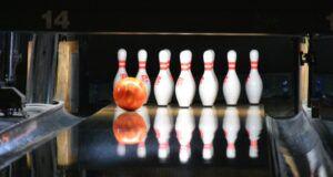 orange bowling ball speeding towards bowling pins