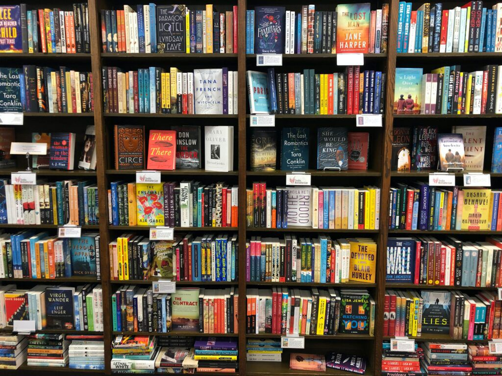 bookstore shelves, with stacks on the floor