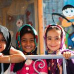 three muslim girls children posing in front of a colorful school wall