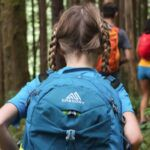 view of child's back as she hikes through the woods on a trail