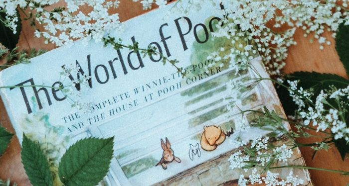 winnie the pooh book surrounded by white flowers