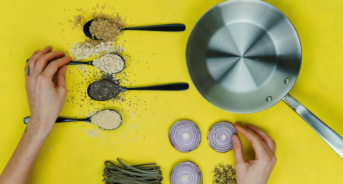 lay flat image of a sauté pan, spoons of spices, and vegetables against a yellow background https://unsplash.com/photos/oQvESMKUkzM