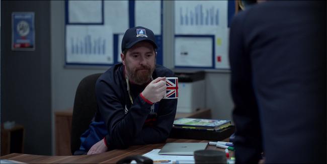 Beard sites at his desk holding a union jack mug