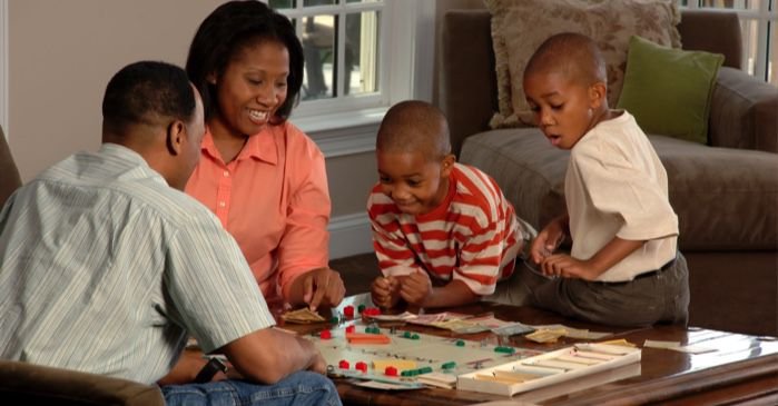 Black family playing monopoly