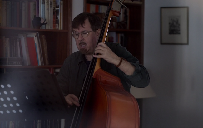 Higgins plays bass in front of his bookcase