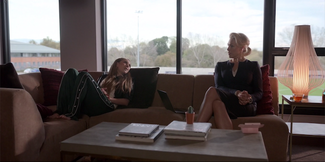 Keeley and Rebecca sit on the couch in her office. Keeley has her bare feet on the couch.