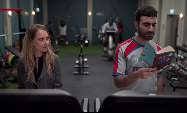 Roy reading A Wrinkle in Time on the treadmill while Keeley glances over at him