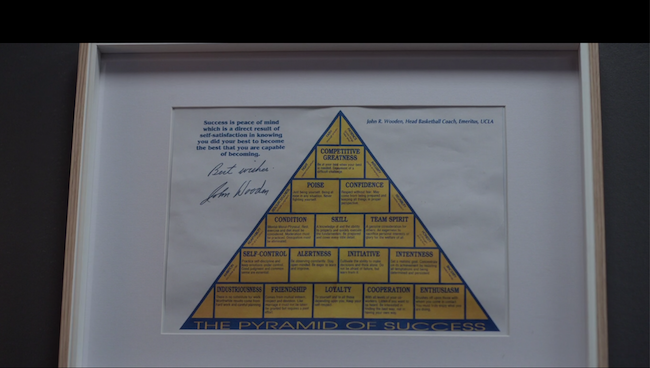 A still from Ted Lasso episode 8, showing a framed Pyramid of Success signed by John Wooden