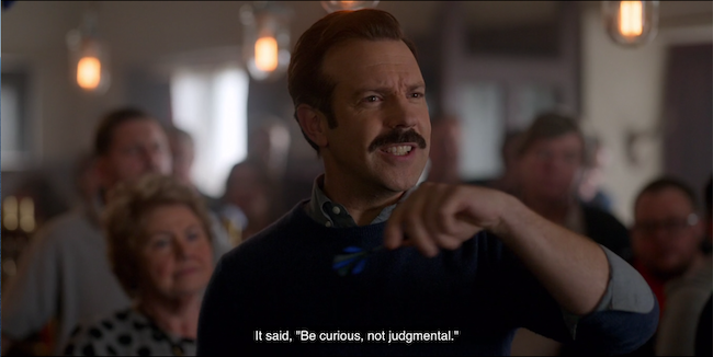 """Ted Lasso at darts with the caption, """"It said, 'Be curious, not judgmental.'"""""""