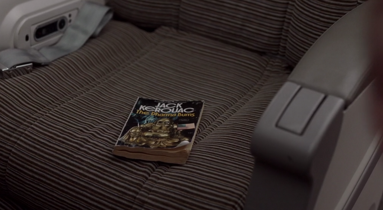 A still of Ted Lasso episode 1 showing a worn copy of The Dharma Bums on Ted's plane seat