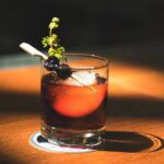 an old fashioned cocktail with a cherry, herb garnish, and spherical ice