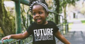 black feminist toddler child wearing a future leader shirt and smiling