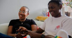 black queer lesbian couple smiling and watching television at home