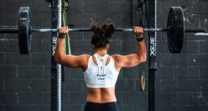 buff woman lifting weights at the gym