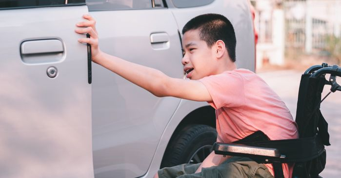 disabled child using a wheelchair opening a car door