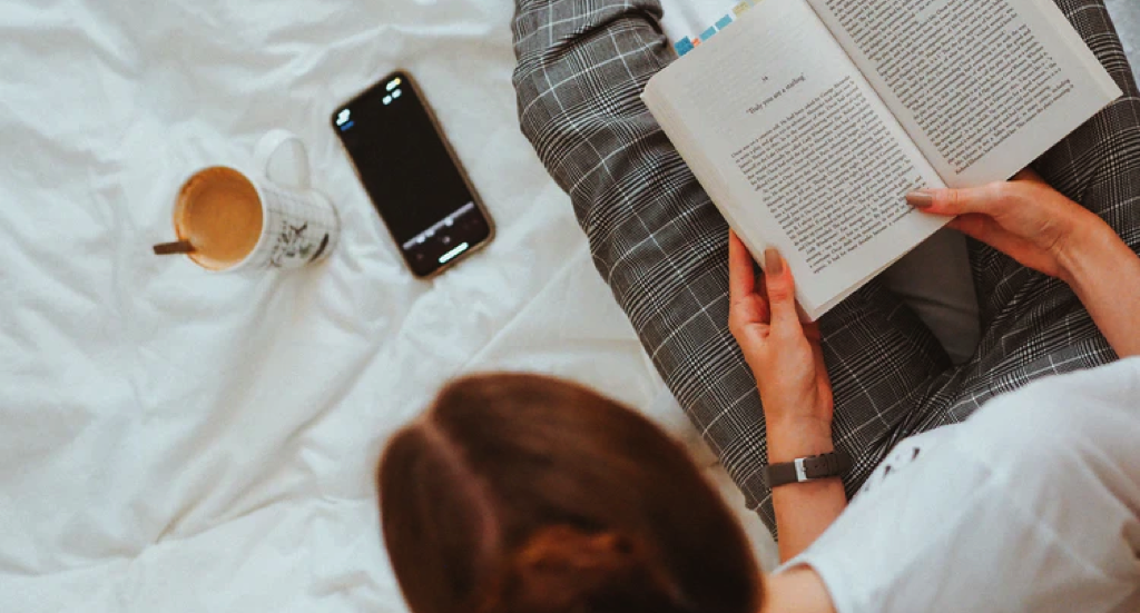person in white shirt and plaid pants with a book in their hands as they glance at their phone https://unsplash.com/photos/X6hQVWGodOU