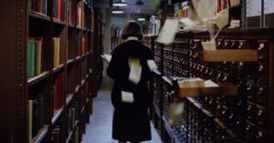 librarian in the library with her back turned to cards from card catalog flying in ghostbusters film still