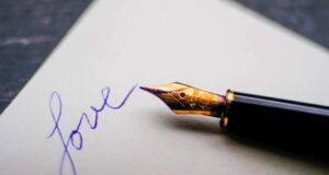 """a black fountain pen on white paper next to the word """"love"""" written in blue ink"""