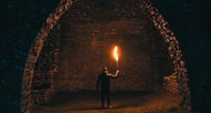 person holding torch in tunnel for horror fantasy feature