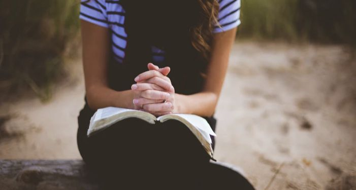 image of a person sitting on a log with their hands folded in an open book in their lap