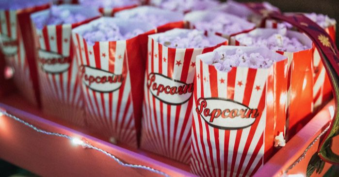 small colorful popcorn bags in a pink box with string lights for movies