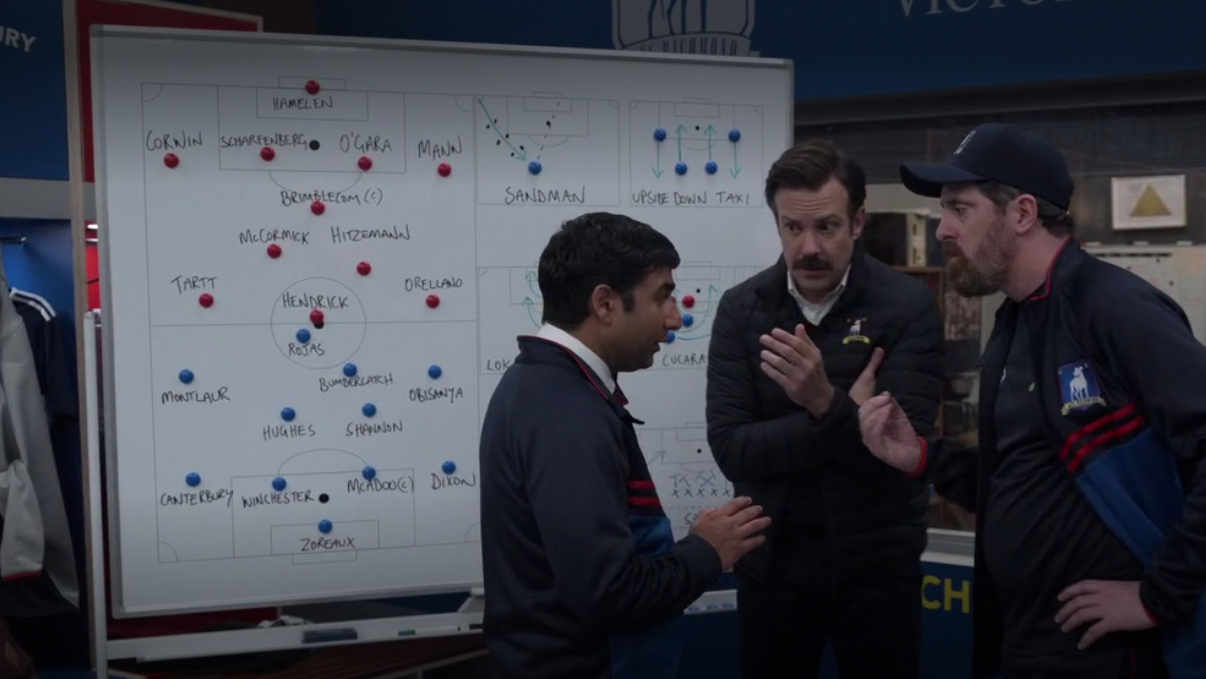 Nate, Ted, and Beard huddle in front of a whiteboard with their plays drawn on it
