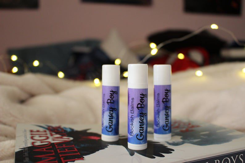 A set of three Gansey Boy labeled lip balms standing on top of The Raven Boys novel.