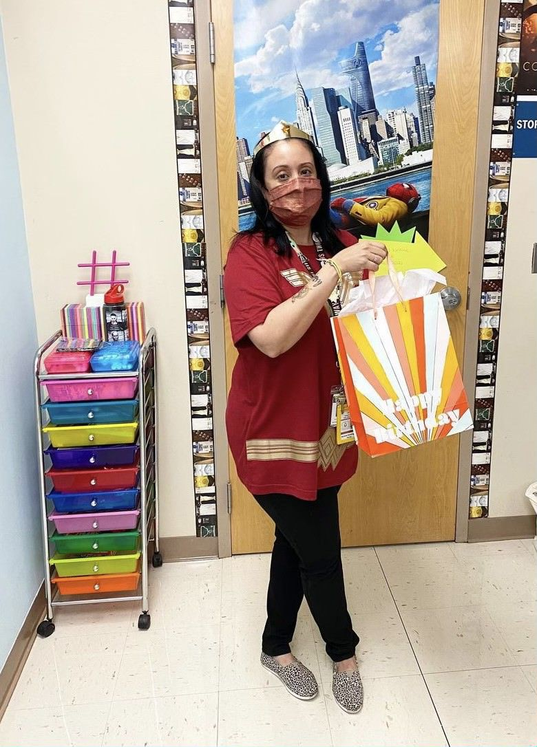 Aurora Dominguez in a Wonder Woman costume and a red face mask holding a birthday gift bag in her classroom at Boca Raton Community High Schoo
