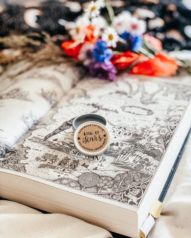 An open lip balm with the label King of Scars sitting on top of an open book with a map