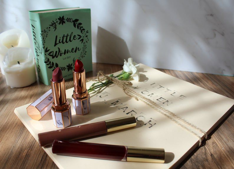 Four lipsticks on top of bound paper labeled Little Women, with the novel Little Women in the background next to two white candles