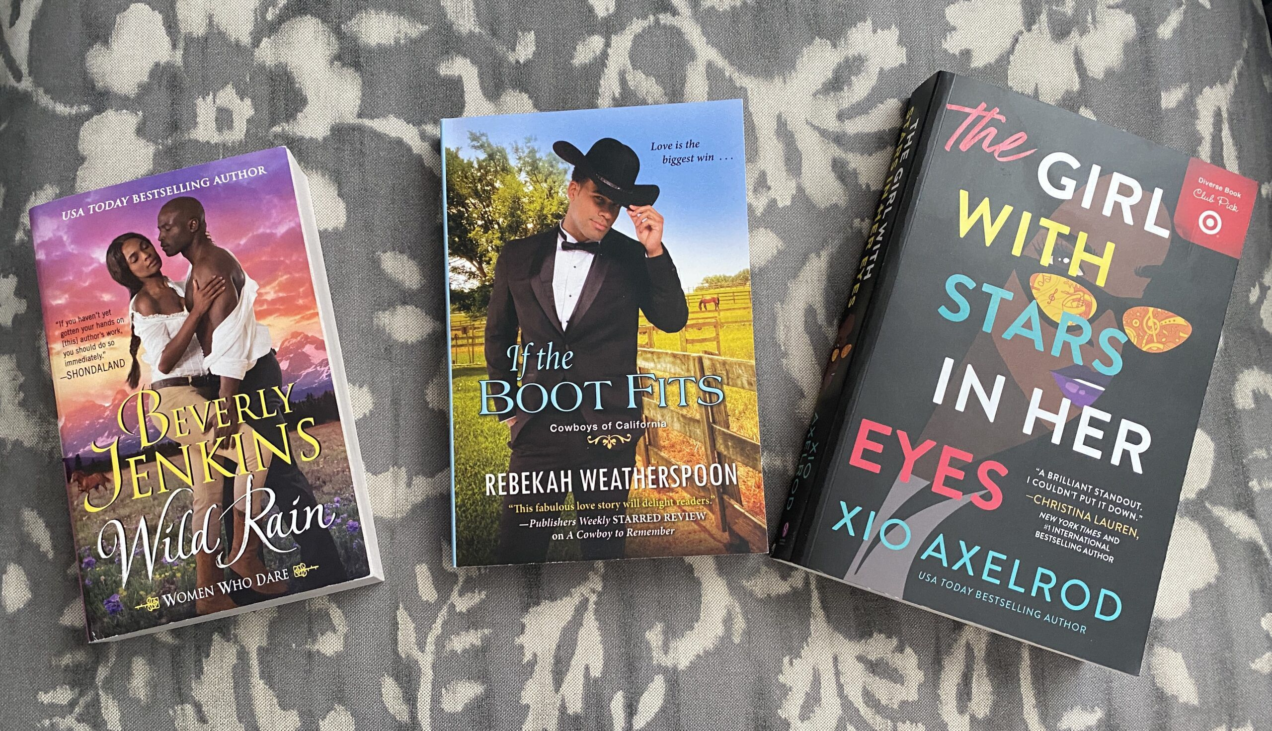 Photograph of three paperback books on a cashmere background.  The book on the left is a mainstream paperback, Wild Rain by Beverly Jenkins.  The middle book is Max Mass, If the Boot Fits by Rebekah Weatherspoon, and the right book is a paperback, The Girl With Stars in Her Eyes by Xio Axelrod.  All three increase in size from left to right.