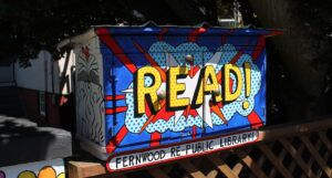 Little Free Library painted with READ! in a comic style