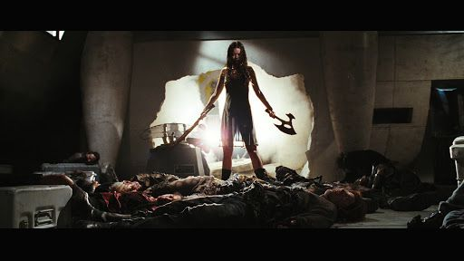 Still from Serenity (2005) of River Tam wielding weapons in each hand, standing over a pile of bodies