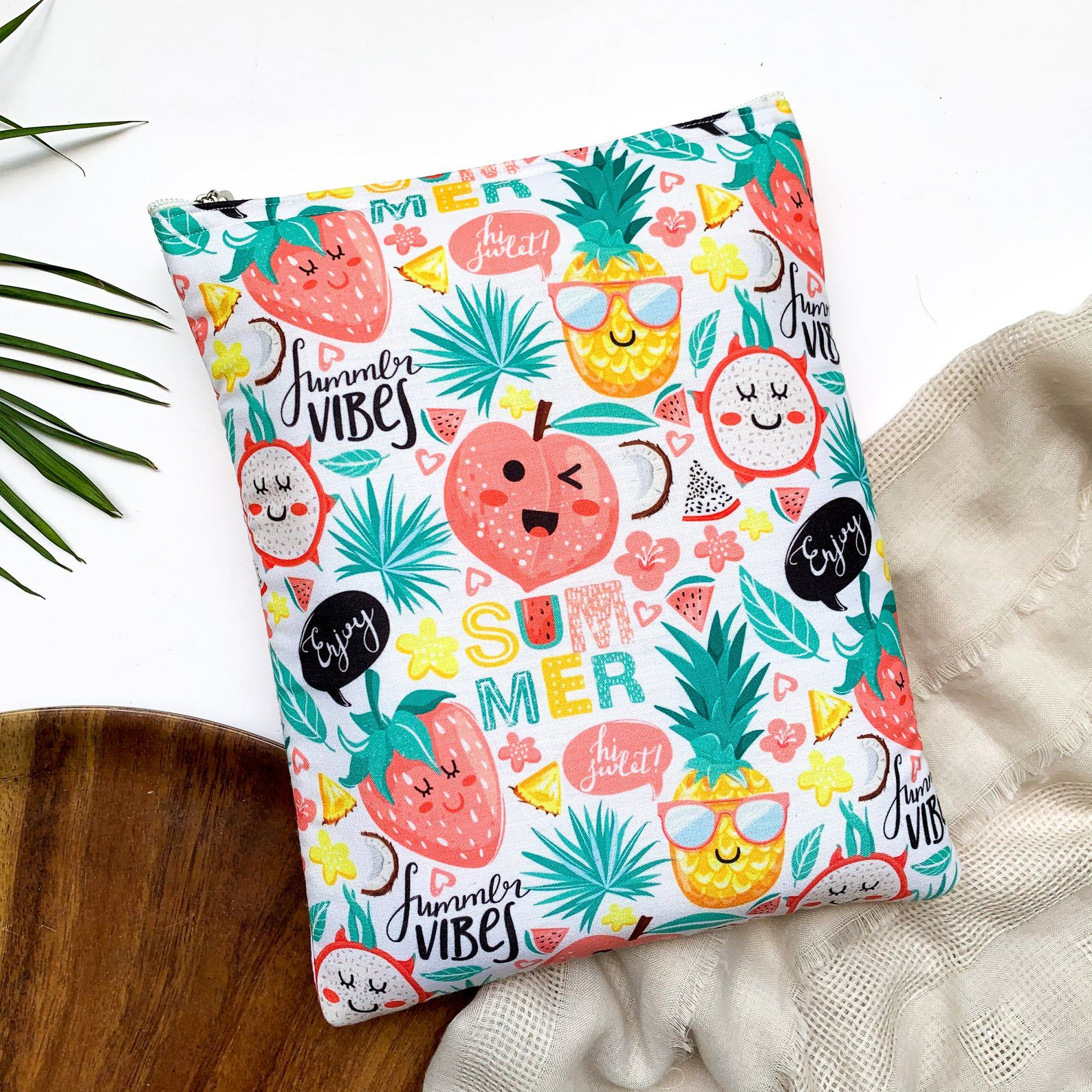 A colourful book sleeve with a white background and a pattern of fruits with happy facial expressions (strawberries, pineapples, watermelonds, etc).