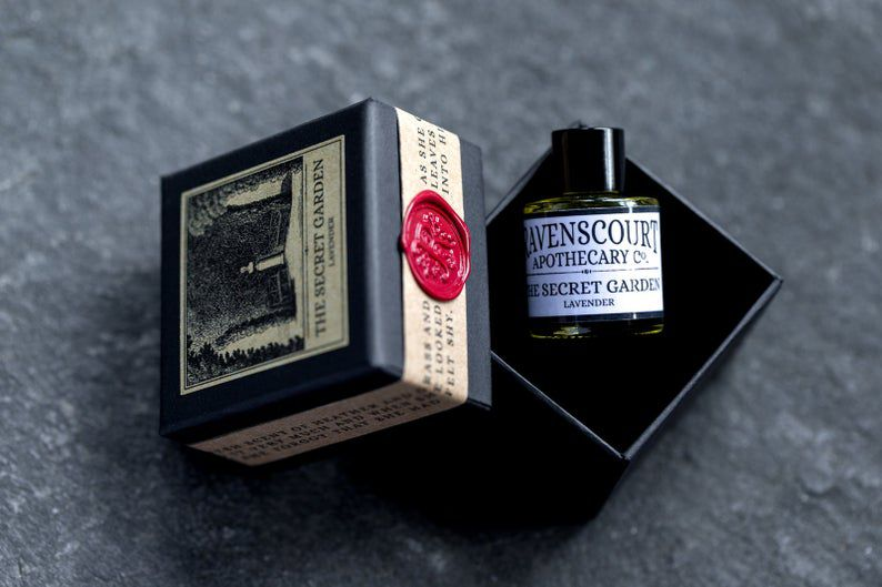 A perfume bottle labeled The Secret Garden sitting in a velvet box, with the box top tilted off to the side