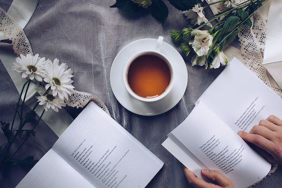 Photo of open poetry books with tea and flowers