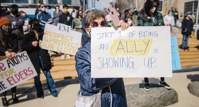 """A photo of a protest sign reading """"Step 1 of being an ally is showing up"""""""
