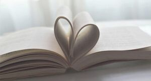 a photo of a book lying open on a table, with pages bent into the shape of a heart