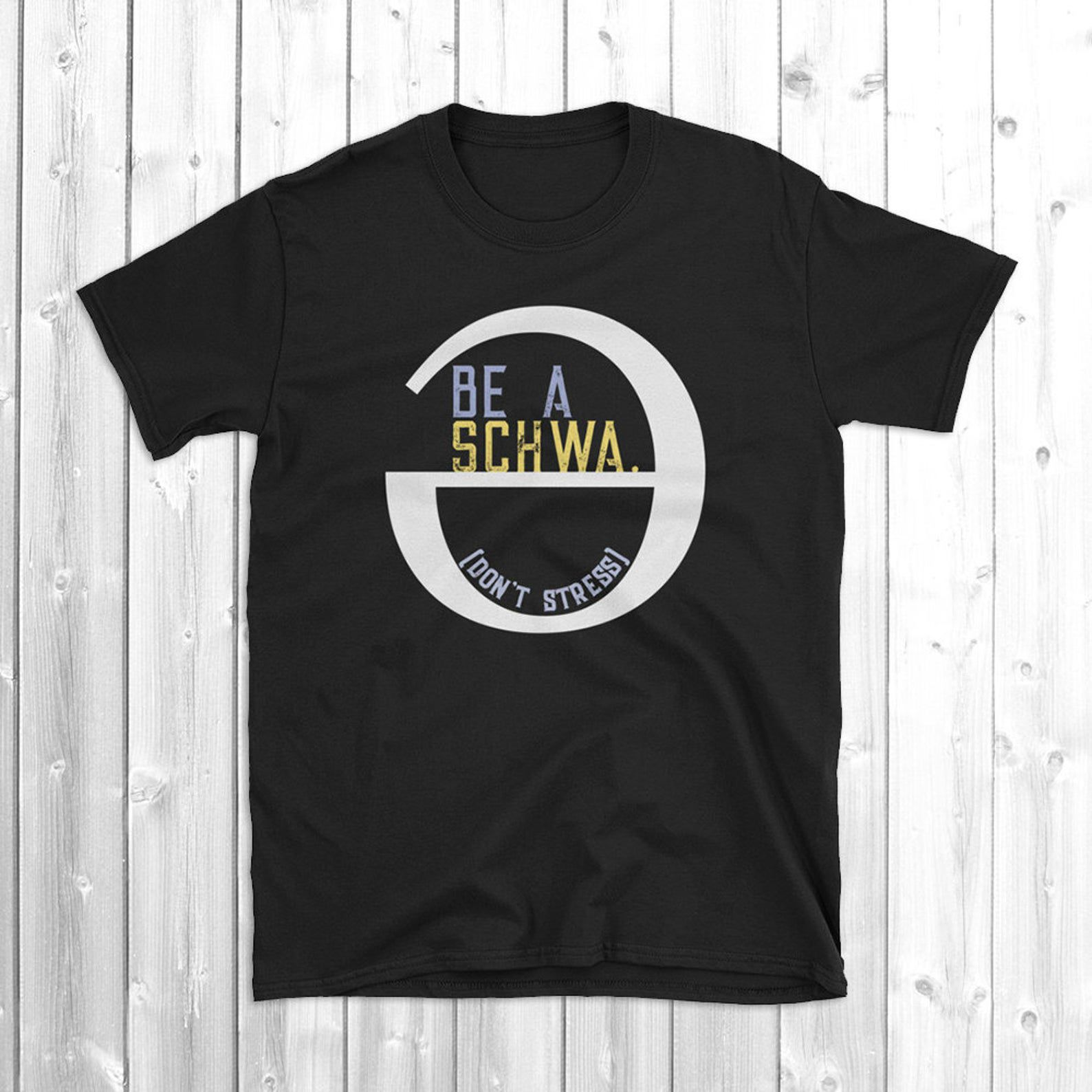"""Black t-shirt with a big white 'schwa' sign on it (an upside-down and backwards e.) The text inside the schwa reads: """"Be a Schwa. [Don't Stress]"""""""