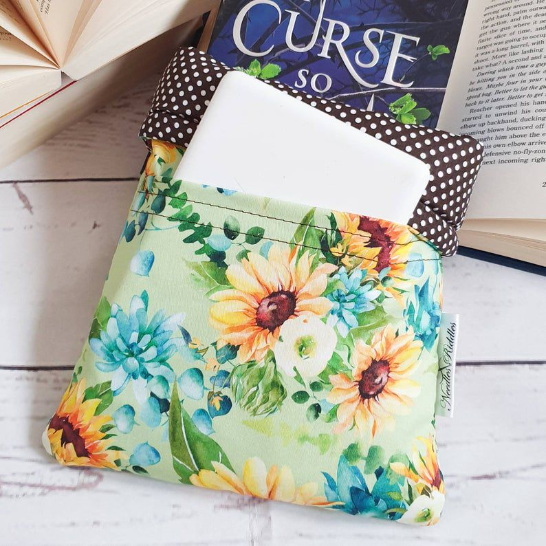 A book sleeve with a book and kindle peeking out. The book sleeve is light green with yellow, blue, and white flower patterns.