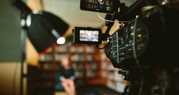 person sitting in front of a camera on a TV or film set; shelves of books are in the background https://unsplash.com/photos/KieCLNzKoBo