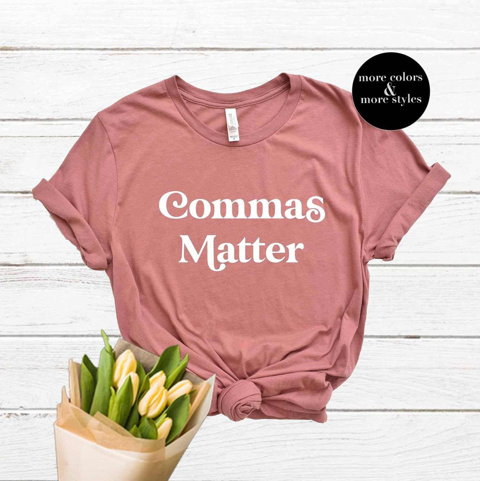 """A pink shirt that says """"Commas matter"""". The small black text box reads """"more colors & more styles,"""" and there is a bouquet of flowers at the bottom of the photo."""