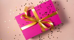 gift box in pink wrapping paper with gold ribbon and confetti