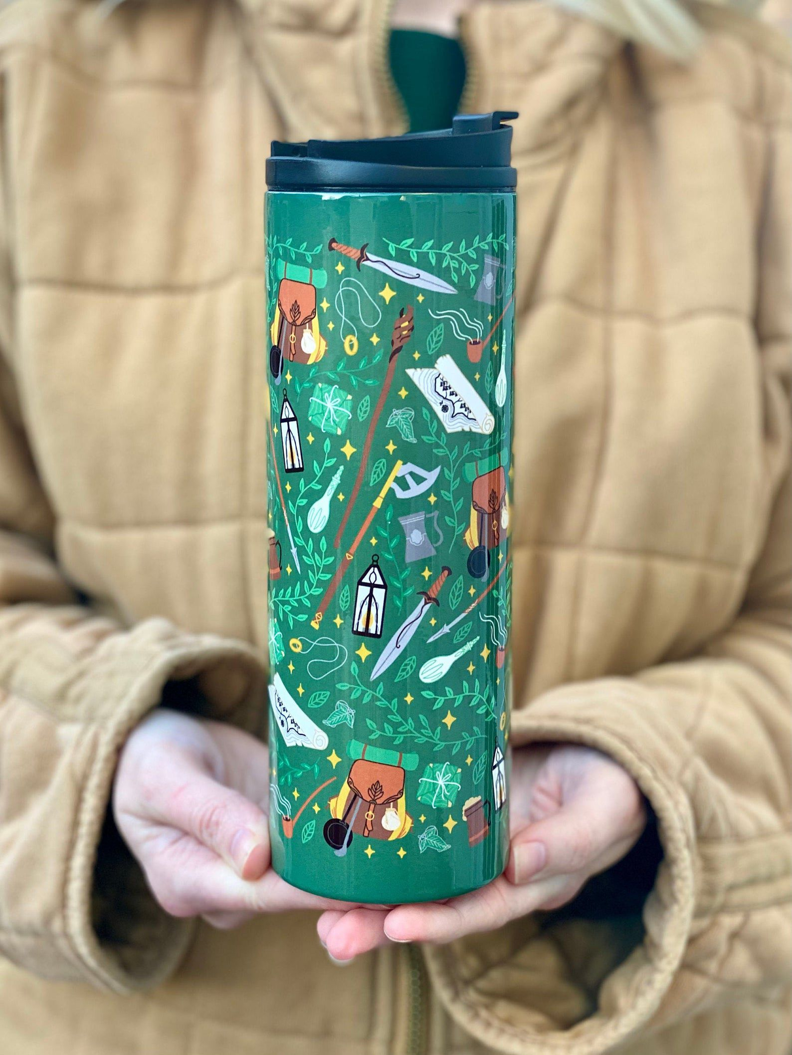 A person holding a tumble in their hands. The tumbler is green with a pattern of leaves, swords, backbacks, and weapons.