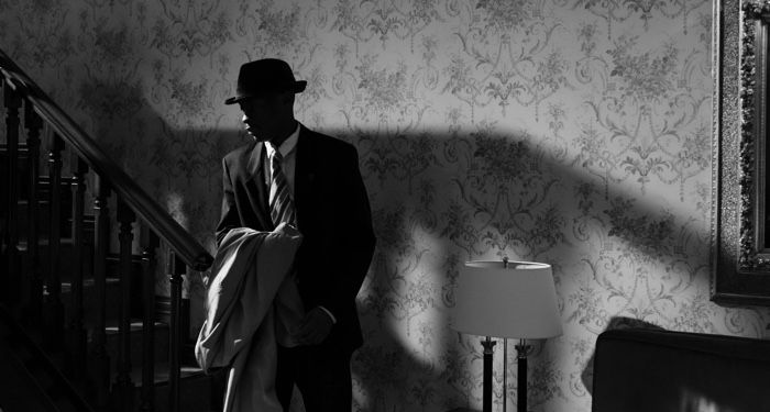 black and white photo of a man in a fedora holding a trench coat at the bottom of a staircase in a wallpapered room https://www.pexels.com/photo/photo-of-man-arriving-home-7319069/