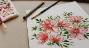 a painting of red and pink flowers on white paper next to various art supplies