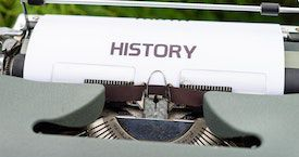 photo credit Markus Winkler. a close-up photo of a typewriter with a page that says HISTORY in big letters positioned in it.