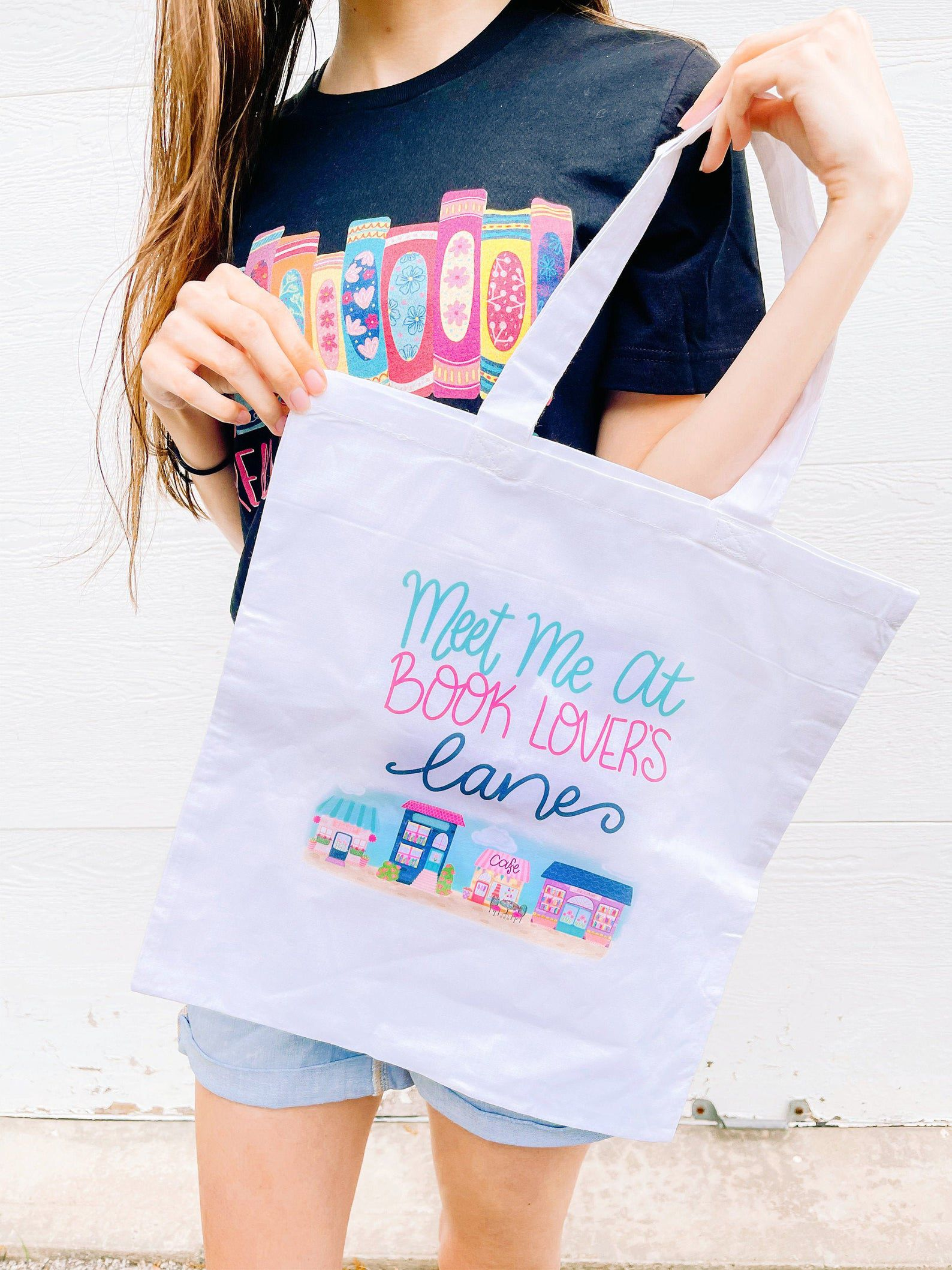 """A woman holding up a tote bag. Tote bag is light purple in colour, includes a colourful image of a town and its buildings, and in colourful letter says """"meet at book lovers lane"""" on top of the image."""